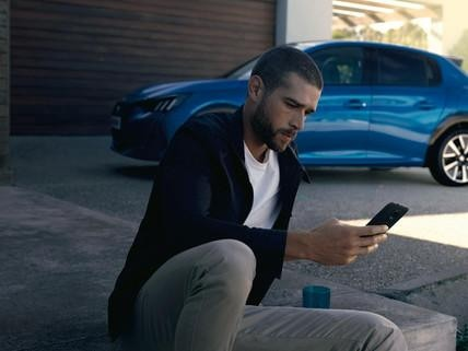 NUOVA PEUGEOT e-208 – Uomo con smartphone, MyPeugeot App
