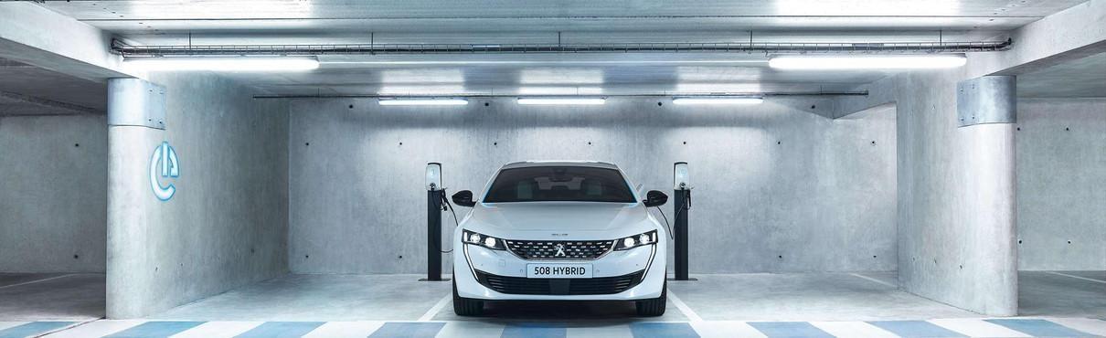 Nuova Peugeot e-208 - Vista posteriore e carica in un punto di ricarica pubblico